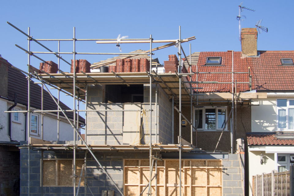 A house / property that is currently undertaking a building project. The house has erected scaffolding surrounding it.